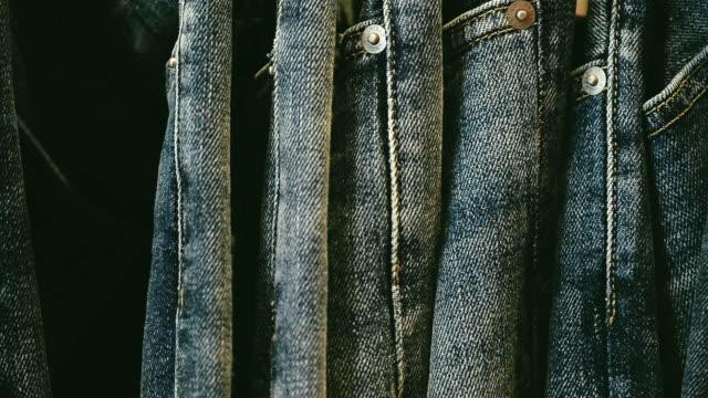 stacks of new blue jeans in the store - dżinsy filmów i materiałów b-roll