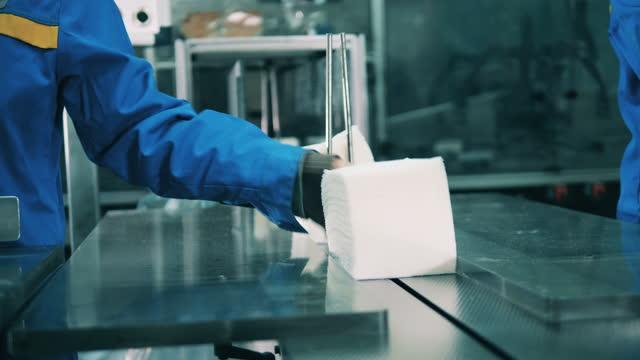 стопки белых тканей лица помещаются на конвейерную ленту - мембрана клетки стоковые видео и кадры b-roll