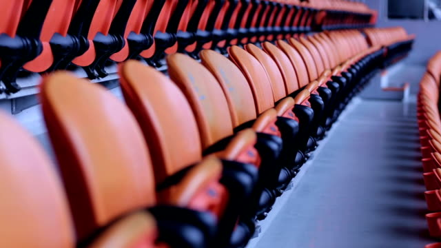 vídeos de stock e filmes b-roll de stadium arena seats chair. rows of orange spectator seating in a sports stadium. - estádio