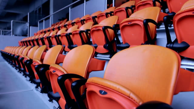 Stadium arena seats chair. Rows of orange spectator seating in a sports stadium. video