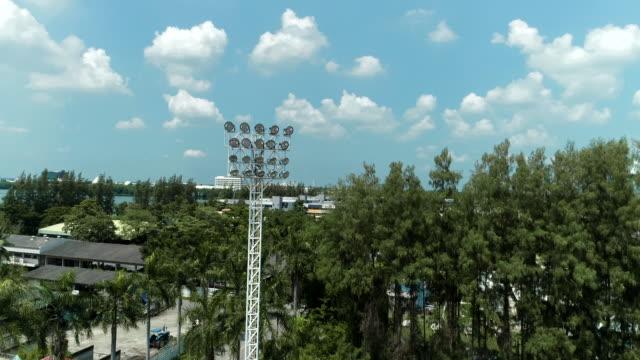 vídeos de stock e filmes b-roll de stadium floodlights shining brightly, drone shot on daylight. - campeão soccer football azul