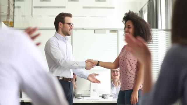 Staff cheering employee of month boss shaking hands express gratitude