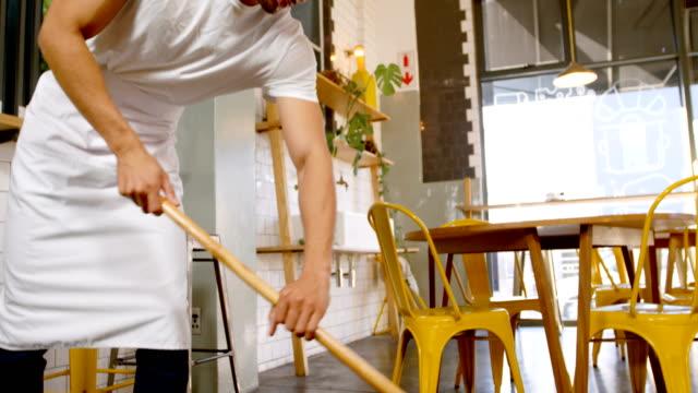 stockvideo's en b-roll-footage met personeel reiniging van de vloer in een café 4k - restaurant table