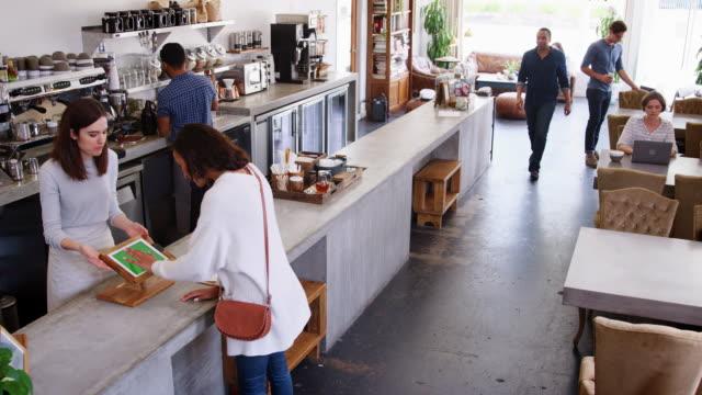 personale al servizio dei clienti in una caffetteria affollata, vista elevata - caffetteria video stock e b–roll