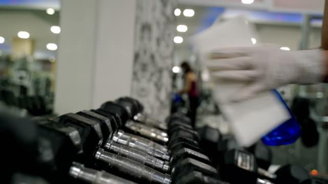 젖은 물티슈와 알코올 소독제 스프레이를 사용하여 체육관에서 러닝 머신을 청소하는 직원. - 체육관 스톡 비디오 및 b-롤 화면