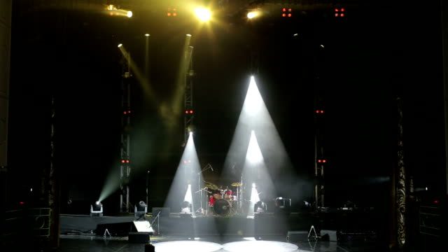 Stage lighting. Light show. Musical instruments and drum set on an empty stage.