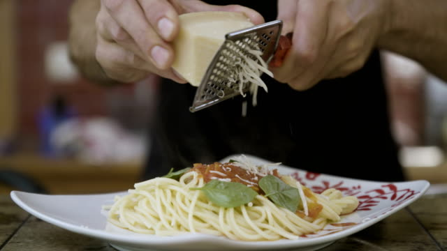 vidéos et rushes de casserole en acier inoxydable sur un poêle de cuisson au gaz - parmesan