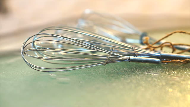 Stainless steel Whisks laying on glass table in modern cooking kitchen video