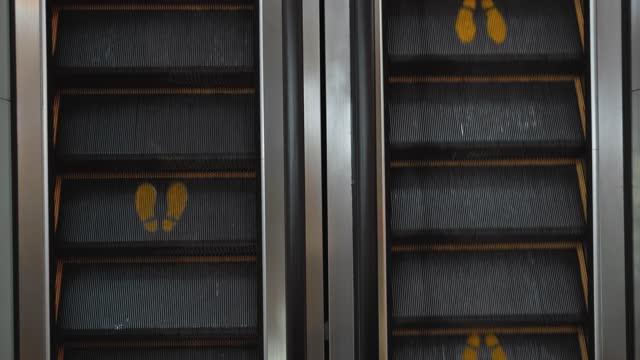 vídeos de stock, filmes e b-roll de escadaria escolator em um shopping center com uma placa de pegada para manter uma distância social - escada rolante