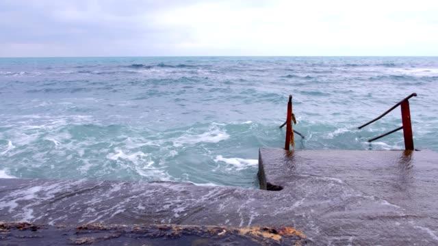 vidéos et rushes de escaliers allant dans la mer agitée. mauvaise journée à la plage avec de grosses vagues. - littoral