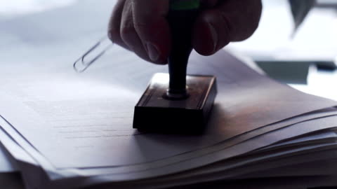 """OK stamp  DE CO WO Close up, slow motion dolly clip of a man's hand rubber stamping a paper document with a red inked """"OK"""" stamp. agreement stock videos & royalty-free footage"""