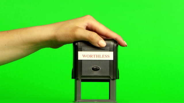 Stamp WORTHLESS. Close up. Green screen Stamp WORTHLESS, put a stamp on the documents, the girl puts a stamp, hand stamp, on a green screen, close up stamp stock videos & royalty-free footage