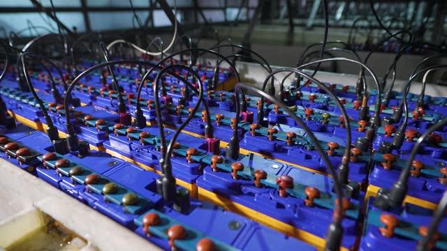 stockvideo's en b-roll-footage met een stand voor het opladen van nieuwe batterijen in de fabriek. autoaccu's zijn in serie aangesloten - lood
