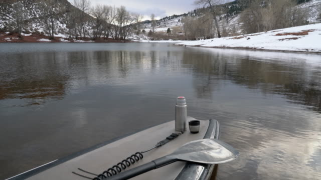 stand up paddleboard with a paddle and hot tea in thermos bottle