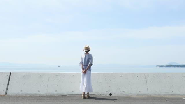 asyalı kadın ayakta, arkadan görünüm - dalgakıran stok videoları ve detay görüntü çekimi