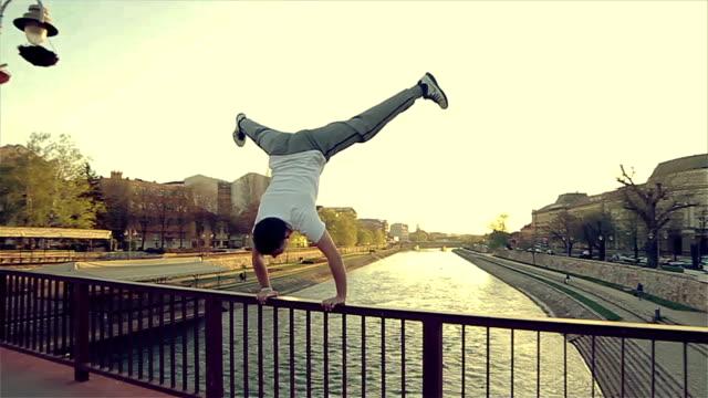står på bron, fantastiska akrobatik skicklighet - styrketräning bildbanksvideor och videomaterial från bakom kulisserna
