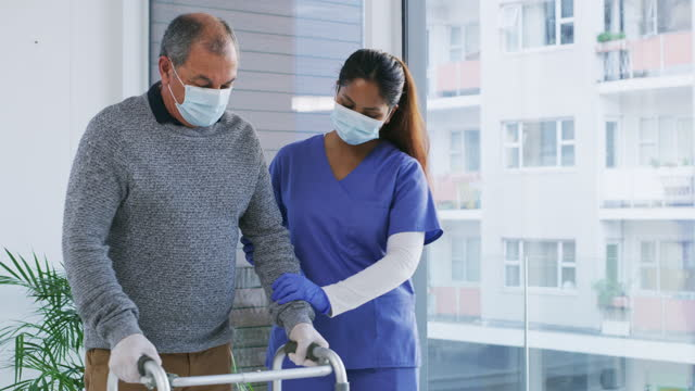 Standing strong in difficult times 4k video footage of a female nurse assisting a senior patient with his walker while wearing masks orthopedic equipment stock videos & royalty-free footage