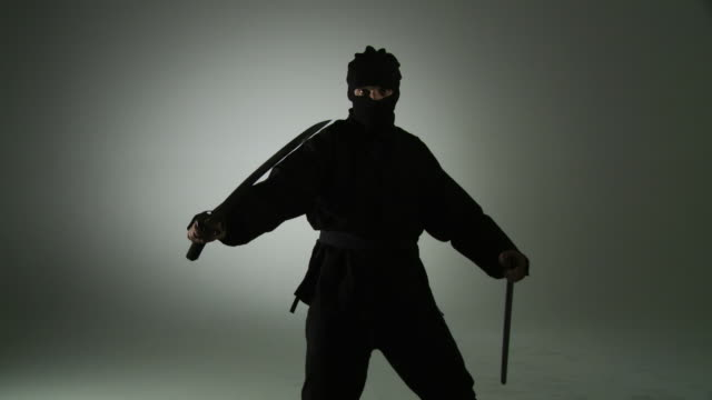 Standing Swordsman Masked ninja assassin unsheathes a sword and turns to face the viewer. martial arts stock videos & royalty-free footage