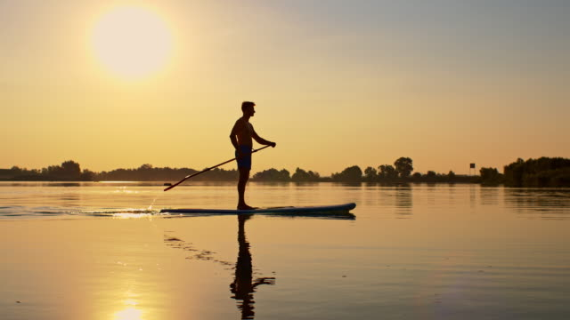SLO MO Stand-up paddleboarding at sunset Two slow motion shots of a silhouette of a young man stand up paddleboarding on the lake. Also available in 4K resolution. recreational pursuit stock videos & royalty-free footage