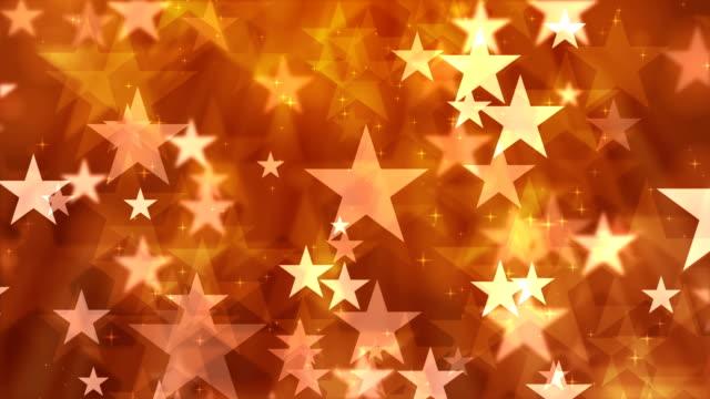 オレンジ色の背景の星の粒子 - 星型点の映像素材/bロール