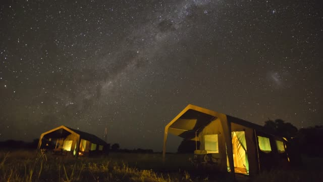 Star time-lapse with the milky way galaxy moving across the night sky of a safari camp in Botswana Star time-lapse with the milky way galaxy moving across the night sky of a safari camp in Botswana makgadikgadi pans national park stock videos & royalty-free footage