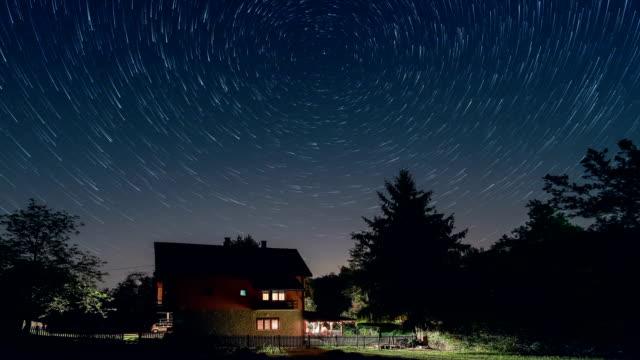 vídeos y material grabado en eventos de stock de lapso de tiempo de senderos de estrellas encima de la casa, a modo de cometa. edificio residencial y los senderos de estrellas en el cielo. - estrella del norte