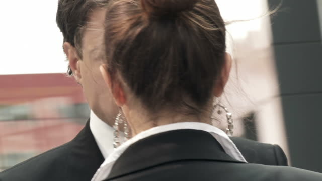 HD SLOW-MOTION: Staring Competition HD720p: SLOW-MOTION shot of a businessman and a businesswoman confronting each other in a staring competition while standing face to face in an urban environment. Spinning point of view. face to face stock videos & royalty-free footage