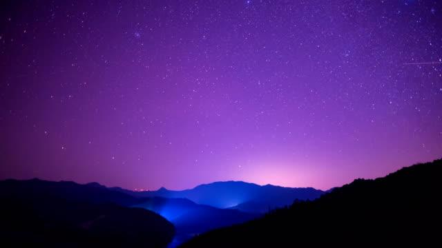 yıldızlı gökyüzü sahne üzerinde inişli çıkışlı tepeler 4 k video - mor stok videoları ve detay görüntü çekimi