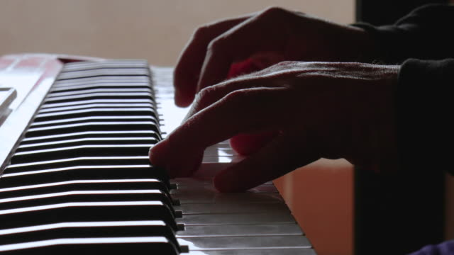 Start of a man playing the piano a sad piece Macro view of a man playing the piano during coronavirus alertness musical theater stock videos & royalty-free footage