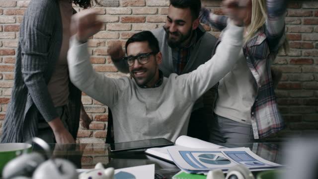start up team celebrating in the office - braccia alzate video stock e b–roll