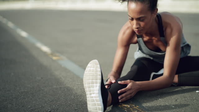 Start with a good few stretches 4k video footage of a sporty young woman stretching while exercising in the city stretching stock videos & royalty-free footage