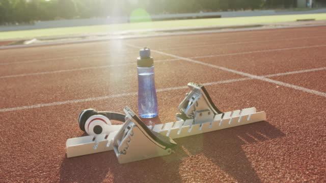 vidéos et rushes de blocs de départ, bouteille d'eau et écouteurs couchés sur les pistes de course - starting block