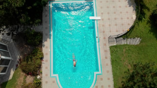 Starting the morning with a jump in the pool Private residential villa with a pool, surrounded with nature. Clear blue water, swimming pool is a perfect place to cool off in summer heat. military private stock videos & royalty-free footage