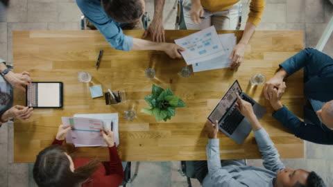 startup meeting room: team von unternehmern, die am konferenztisch sitzen, diskutieren, probleme lösen, digitaltablet, laptop verwenden, dokumente mit statistiken teilen, diagramme. top-ansicht zoom out - kommunikation themengebiet stock-videos und b-roll-filmmaterial