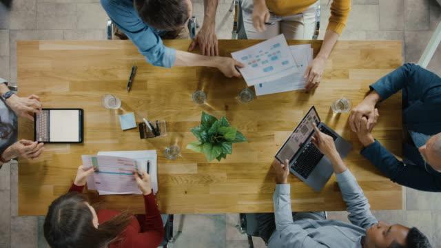 stockvideo's en b-roll-footage met opstarten vergaderruimte: team van ondernemers zittend op de conferentietafel hebben discussies, problemen oplossen, gebruik maken van digitale tablet, laptop, delen van documenten met statistieken, grafieken. bovenaanzicht uitzoomen - marketing planning