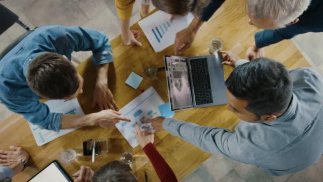 vidéos et rushes de salle de réunion de démarrage : l'équipe d'entrepreneurs debout autour de la table de conférence ont des discussions, résolvent des problèmes, emploient la tablette numérique, l'ordinateur portable, partagent des documents avec des statistiques, des - marketing