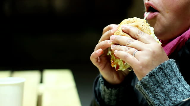 Starving poor woman eating large portion of junk food, biting video