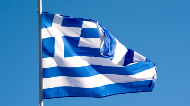 State Flag of Greece The Big State Flag is illuminated by the sun and flutters epically in the wind against the blue sky. Slow Motion 120 fps athens greece stock videos & royalty-free footage