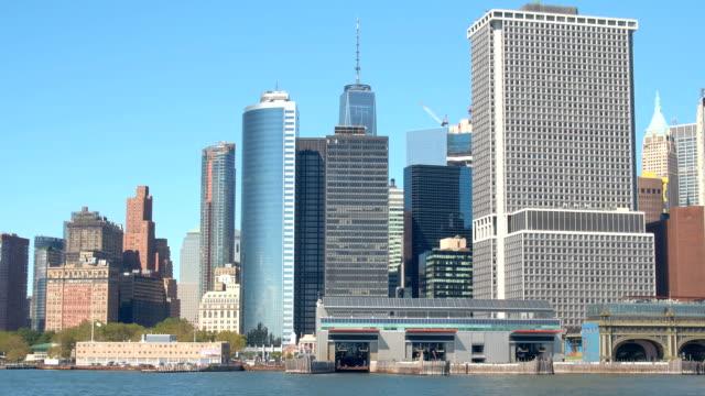 närbild: staten island ferry byggnad, glasartade skyskrapor i downtown manhattan - flod vatten brygga bildbanksvideor och videomaterial från bakom kulisserna