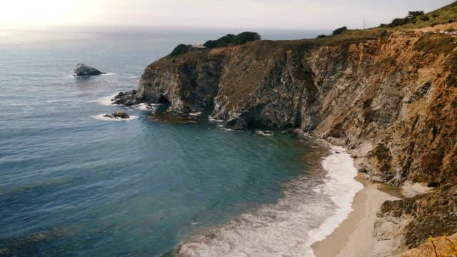 vídeos de stock e filmes b-roll de static panoramic shot of amazing summer ocean beach coastline rocks at beautiful epic big sur vista point, california. - estrada 001