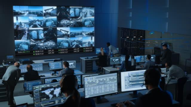 stockvideo's en b-roll-footage met static shot van een groep professionals werken in een surveillance control center met cctv video footage van een industriële fabriek op een groot digitaal scherm. medewerkers van de controlekamer zitten voor computers. - gefabriceerd object