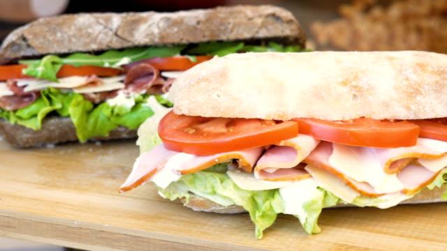 statiska skott av en kalkon och en balkan smörgås med sallad, rucola - cheese sandwich bildbanksvideor och videomaterial från bakom kulisserna