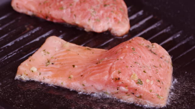 Static shot of fresh salmon cooking on a grilling pan video