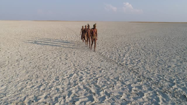 Static then, zoom out aerial view of four San Bushmen walking in single file across the vast expanse of the Makgadikgadi Pans, Botswana