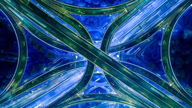 vídeos de stock, filmes e b-roll de top vertical estática abaixo vista aérea de tráfego na rodovia intercâmbio à noite. fundo de timelapse 4k uhd - estrada principal estrada