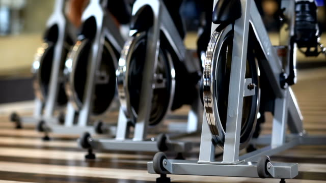 Stationary Bicycles Low angle shot of exercising bicycles in the gym. 60FPS. exercise bike stock videos & royalty-free footage