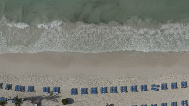 Stationary drone shot over breaking waves in the surf on tropical beach with deckchairs video