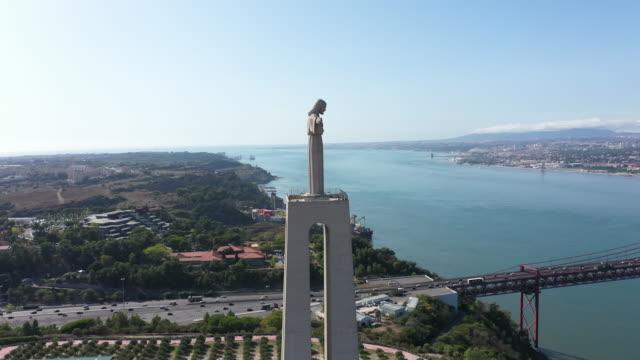 vídeos de stock e filmes b-roll de statue of cristo rei under lisbon estuary - lisboa