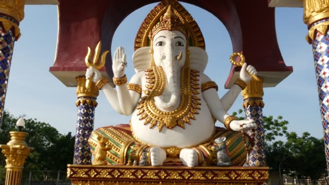 Statue of Ganesha in Hindu temple. Statue of Ganapati with golden decorations and elephant head located in yard of traditional Hindu temple on sunny day in Asian country. Wat Plai Laem. Koh Samui.