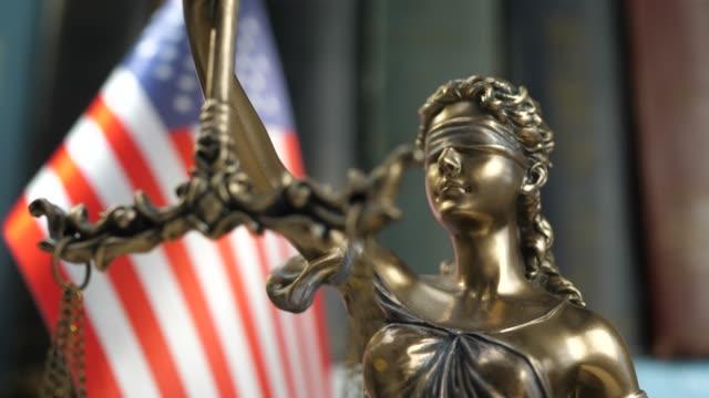 staty av lady justice med böcker och usa flagga - domstol bildbanksvideor och videomaterial från bakom kulisserna